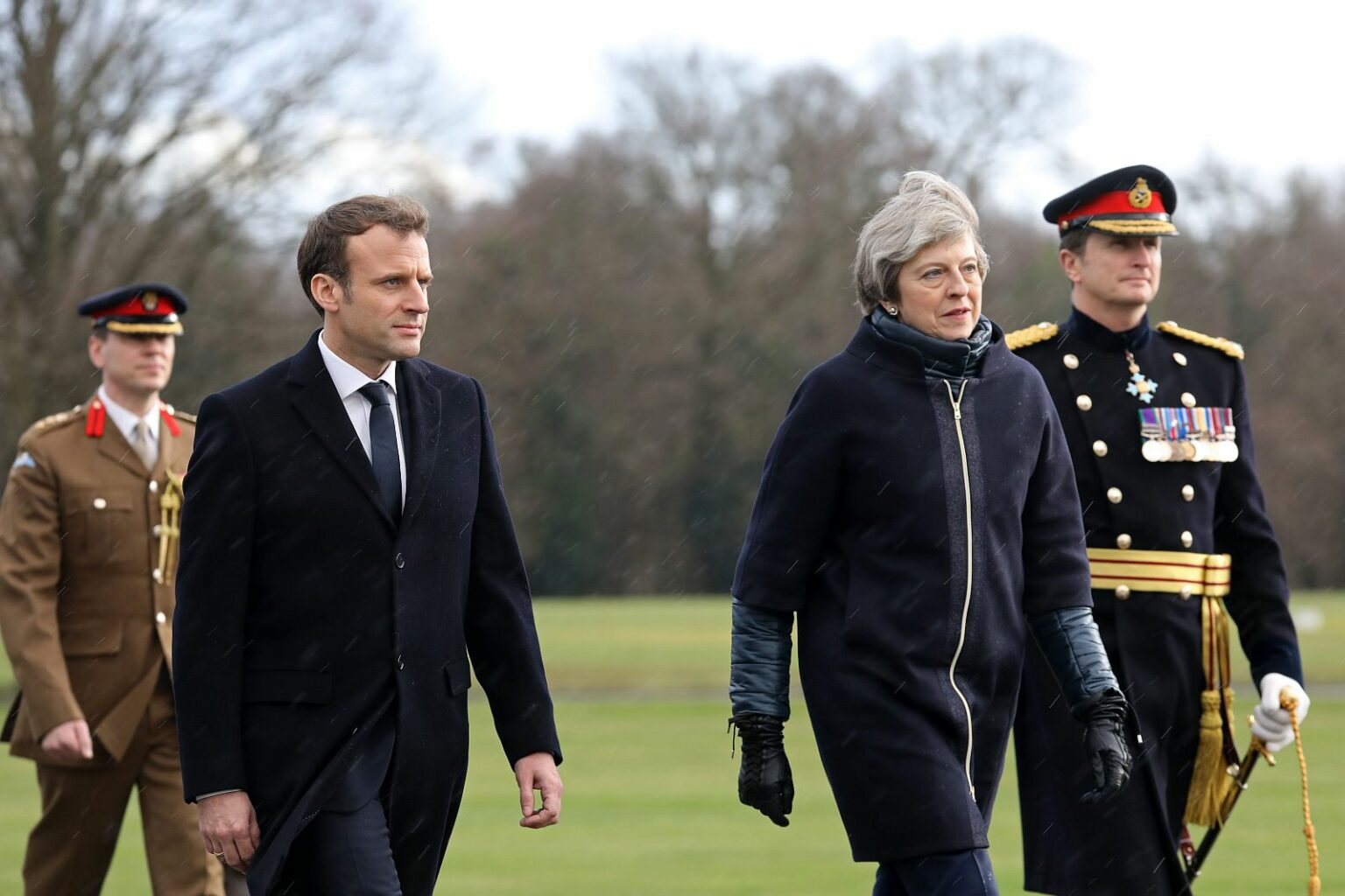 French President Emmanuel Macron (2nd L) and Britain's Prime Minister Theresa May (2nd R) arrive to review an honour guard at the Royal Military Academy Sandhurst, west of London on January 18, 2018. President Macron will take part in a Franco-British summit.
