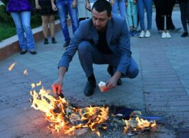 A participant in a protest in Simferopol against missile strikes on Syria burns images of US President Donald Trump, French President Emmanuel Macron and British Prime Minister Theresa May. Russian attitudes towards Donald Trump have changed since he took office.