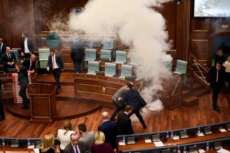 Kosovo's lawmakers react after opposition members released a teargas canister inside the country's parliament in Pristina on March 21, 2018 before a vote for an agreement to ratify or not a border demarcation deal signed in 2015 with Montenegro.