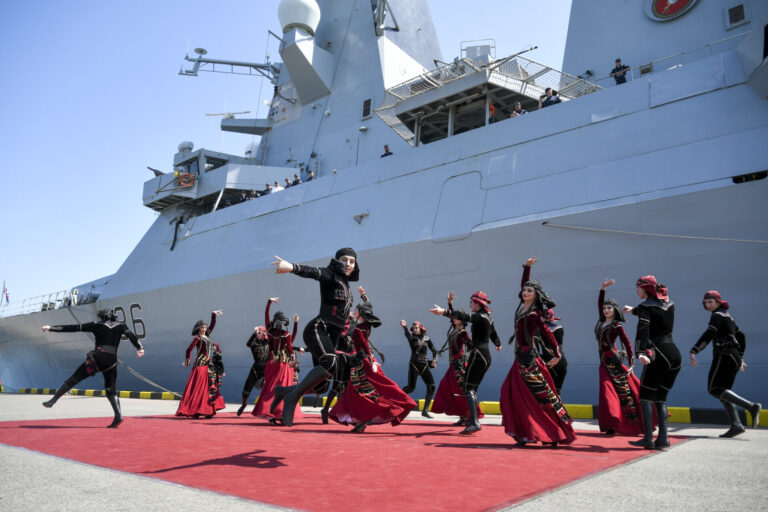 """Georgians wearing national costumes dance in front of the British destroyer, HMS Defender, upon its arrival at the port of Batumi in June 2021. """"The British naval presence in the Black Sea has grown to uphold freedom of navigation and remind the Kremlin that the annexation of Crimea is not a done deal,"""" James Rogers writes."""