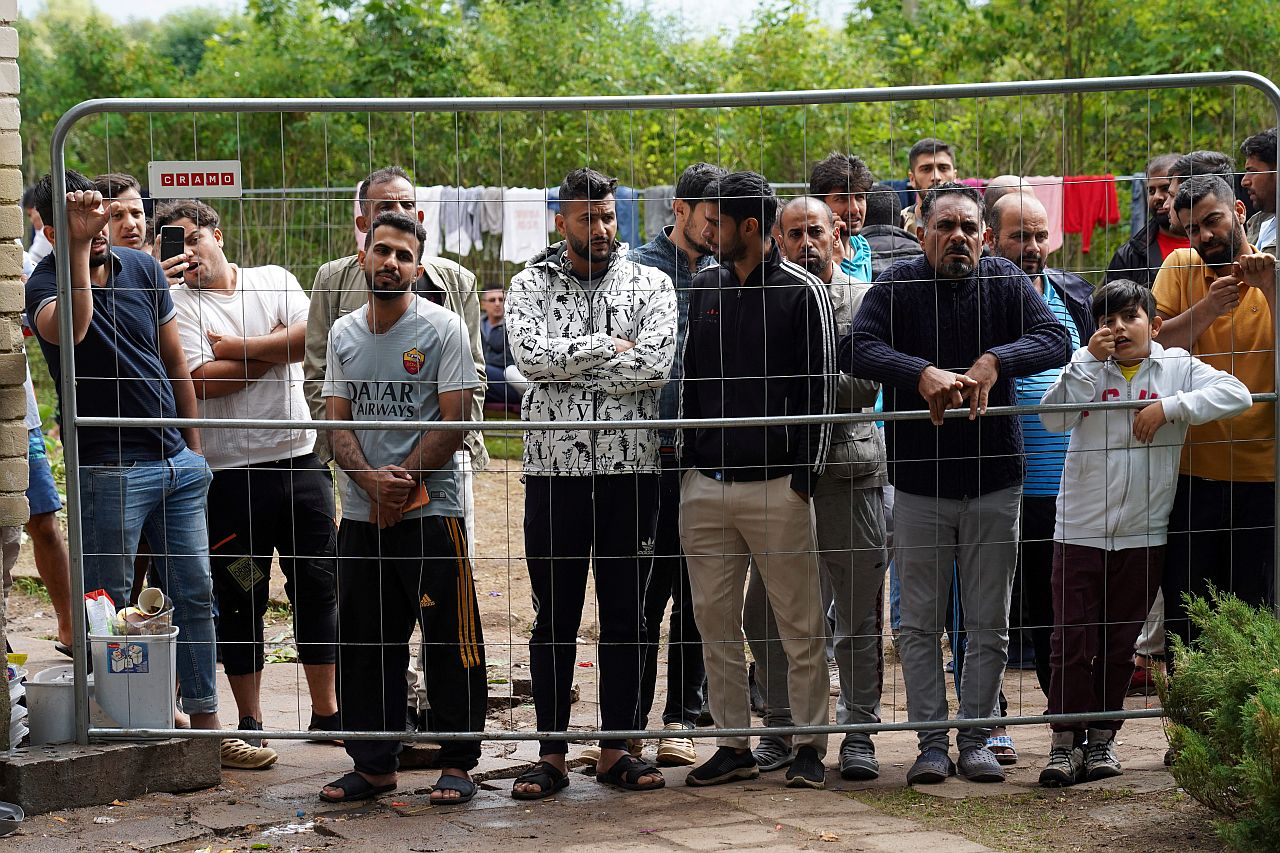 Migrants gather near a fence at a temporary detention center in Kazitiskis, Lithuania in August 2021.